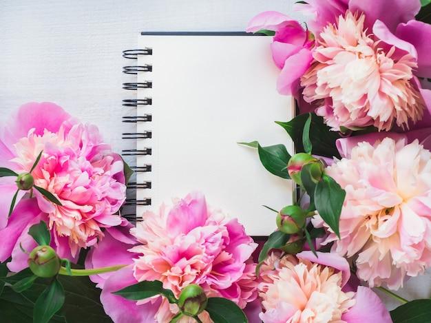 Blumenmuster von blühenden pfingstrosenblumen und -skizzenbuch