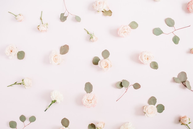 Blumenmustertextur aus beigefarbenen rosen, eukalyptuszweigen auf blassem pastellrosa hintergrund. flache lage, ansicht von oben