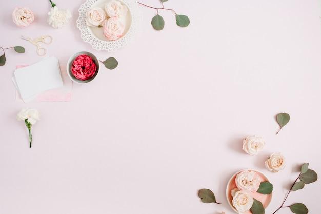Blumenrahmen aus beige und roten rosen und weißer nelke auf blassem pastellrosa hintergrund. flache lage, ansicht von oben