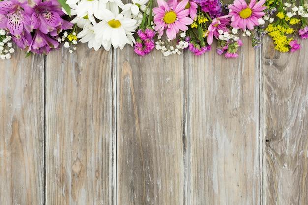 Blumenrahmen der draufsicht mit hölzernem hintergrund