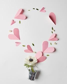 Blumenrahmen in einem eimer und papierherzen mit copyspace, flach liegen