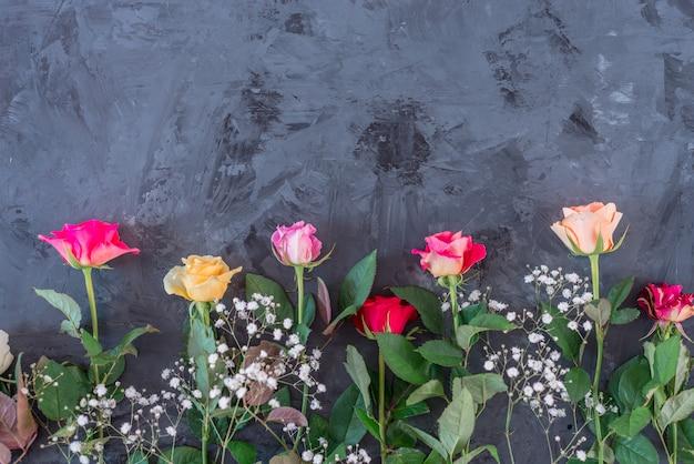 Blumenrahmen mit bunten rosen auf grauem / schwarzem hintergrund, flache lage, draufsicht