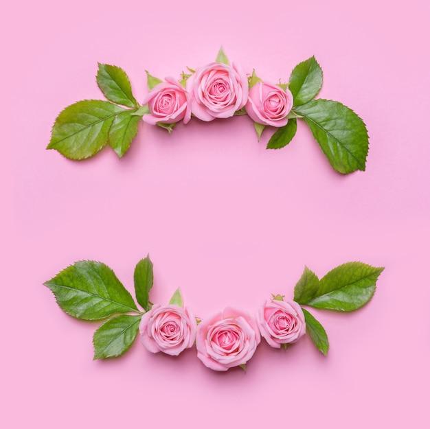 Blumenrahmen mit rosa rosen auf einem rosa hintergrund. blumenrand. muster für einladungskarte. flaches design, blick von oben