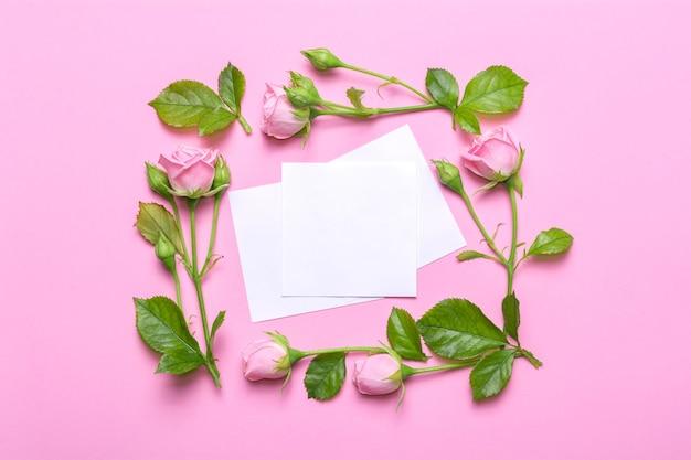 Blumenrahmen mit rosa rosen auf einem rosa hintergrund.