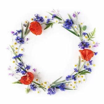 Blumenrahmen mit roten mohnblumen, kamillenblüten, kornblumen und grünen zweigen
