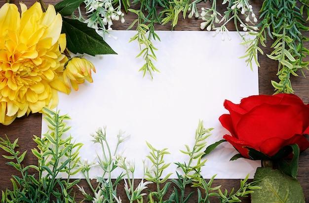 Blumenrahmen mit weißem leerem papier auf hölzernem hintergrund