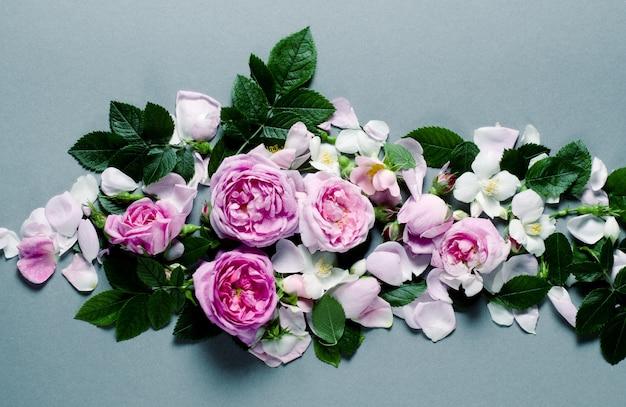 Blumenrahmen. rosenblüten auf grauem hintergrund. flach liegen