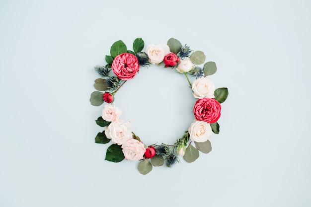 Blumenrahmenkranz aus beige und roten rosen, eukalyptuszweige auf hellpastellblauem hintergrund. flache lage, ansicht von oben
