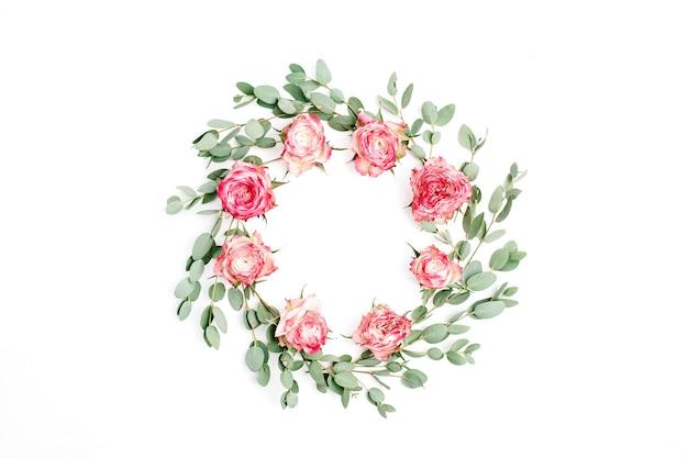 Blumenrahmenkranz aus roten rosenblüten und eukalyptuszweigen auf weißem hintergrund. flache lage, ansicht von oben