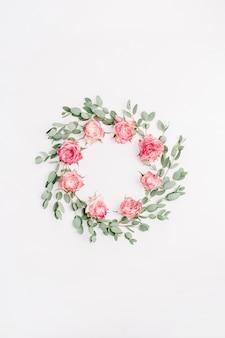 Blumenrahmenkranz aus roten rosenblüten und eukalyptuszweigen isoliert auf weißem hintergrund. flache lage, ansicht von oben