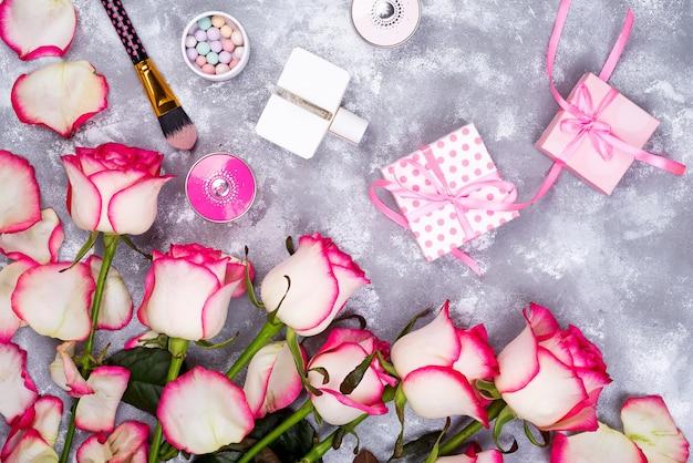 Blumenrahmenzusammensetzung mit rosen und geschenkbox auf steinhintergrund. flach legen,. valentinstag