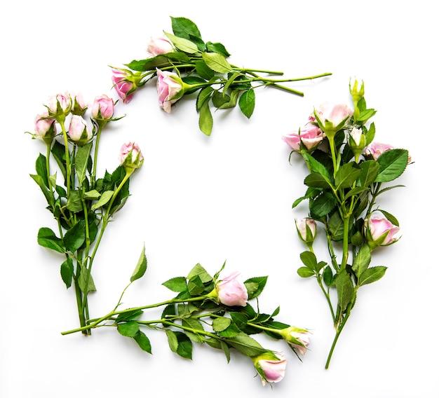 Blumenrand mit leerzeichen. rahmen der rosa rosen und der blütenblätter auf weißem hintergrund. muttertagsgrußkartenentwurf. hochzeitseinladung. blumenarrangement