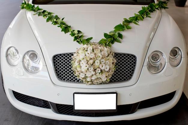 Blumenschmuck in kugelform schmücken vor dem kühlergrill des autos. die hochzeitsblume.