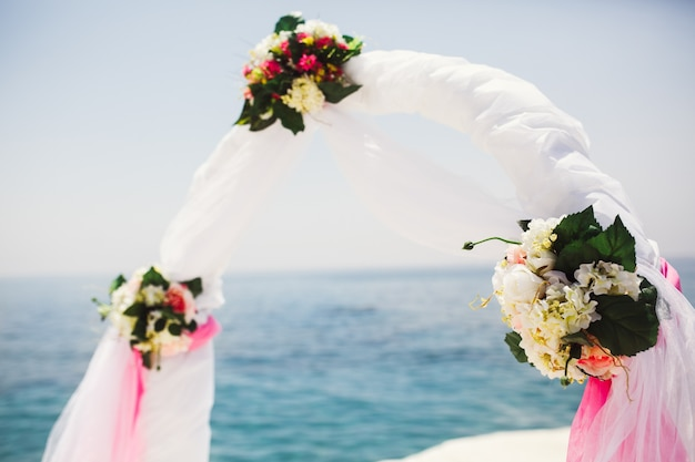 Blumensträuße aus weißen blumen schmücken einen hochzeitsaltar