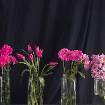 Blumensträuße mit rosa blumen in vasen