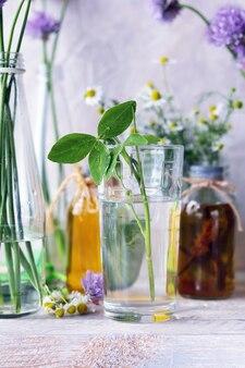 Blumensträuße und tinkturen aus heilkräutern in glasbehältern auf einem holztisch
