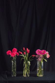 Blumensträuße von rosa blumen in vasen mit wasser
