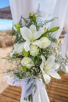Blumenstrauß an einem hochzeitsbogen für das brautpaar.