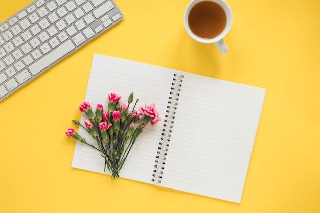 Blumenstrauß auf notizbuch nahe schale des getränks und der tastatur
