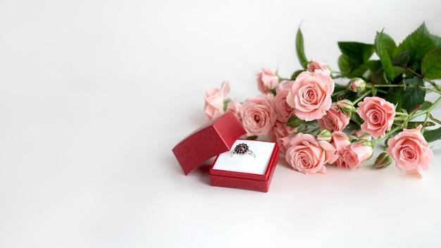 Blumenstrauß aus blassrosa rosen und verlobungsring mit juwelen in geöffneter roter schmuckschatulle. valentinstag feiern