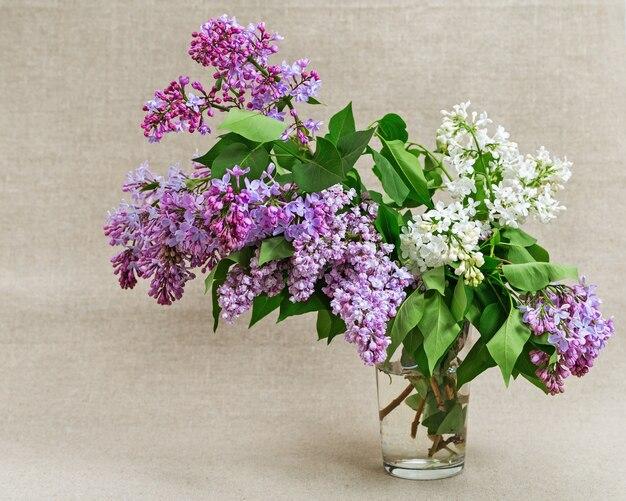 Blumenstrauß aus flieder in glasvase. frische blumen lila.