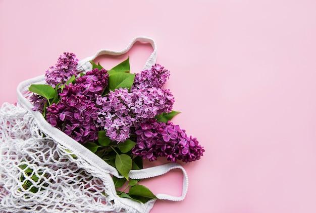 Blumenstrauß aus flieder in wiederverwendbarer einkaufstasche aus öko-netz auf rosa oberfläche. konzept kein kunststoff, kein abfall. kopierraum draufsicht vorlage für grußkarte, postkarte, einladung.