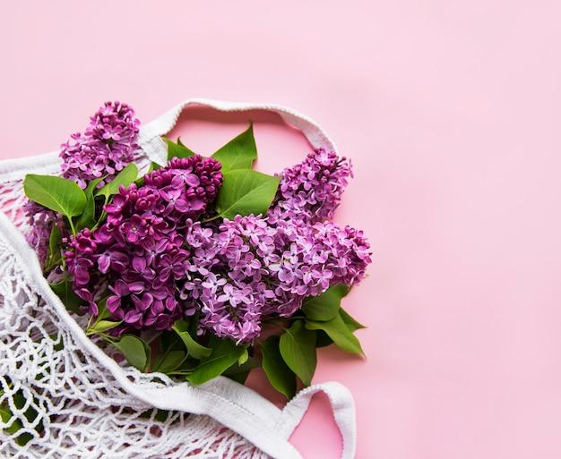 Blumenstrauß aus flieder in wiederverwendbarer einkaufstasche aus öko-netz auf rosa oberfläche