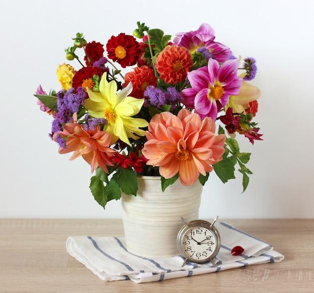 Blumenstrauß aus gartendahlien im eimer auf dem tisch und ein metall-retro-wecker-stillleben im rustikalen stil, helle sommerkomposition mit blumen und einer uhr