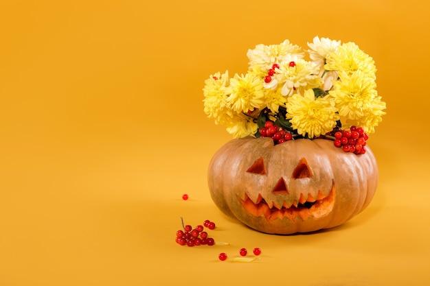 Blumenstrauß aus gelben herbstblumen in einem kürbis. halloween