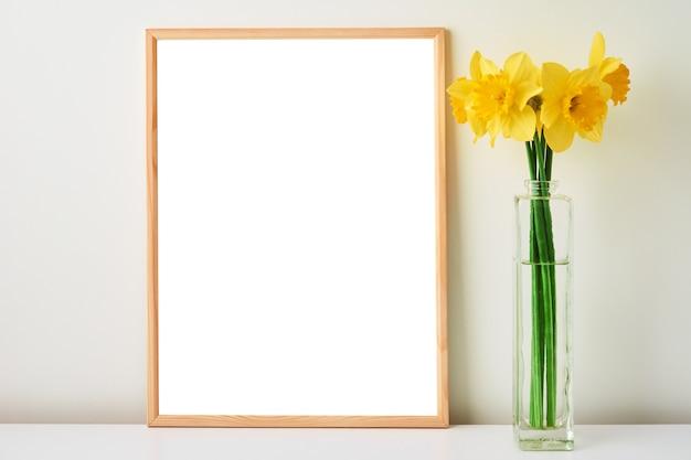Blumenstrauß aus gelben narzissenblumen in glasvase und leerem rahmen auf weißem hintergrund mock-up