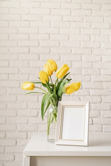 Blumenstrauß aus gelben tulpen in einer glasvase und einem leeren fotorahmen auf einem weißen backsteinmauerhintergrund. mock-up-design
