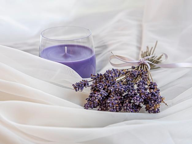Blumenstrauß aus getrocknetem lavendel, gebunden mit einem band und der duftkerze aus lavendel liegt auf einem weißen, luftigen stoff. tiefenschärfe mit geringer schärfentiefe. harmonie.