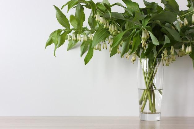 Blumenstrauß aus grünen zweigen mit weißen blumen in einer glasvase auf dem tisch.