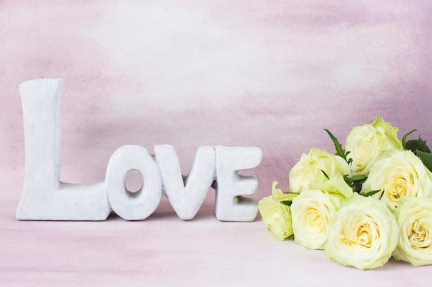 Blumenstrauß aus hellen rosen und das wort liebe aus stein