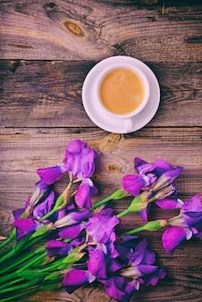 Blumenstrauß aus iris und einer tasse kaffee