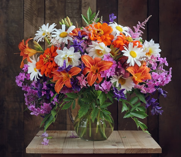 Blumenstrauß aus kulturblumen in einer vase. gänseblümchen und lilien, phlox und dahlien.