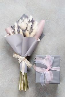 Blumenstrauß aus lavendel und lagurus in grau-lila verpackung mit einer geschenkbox in einer einzigen farbe.