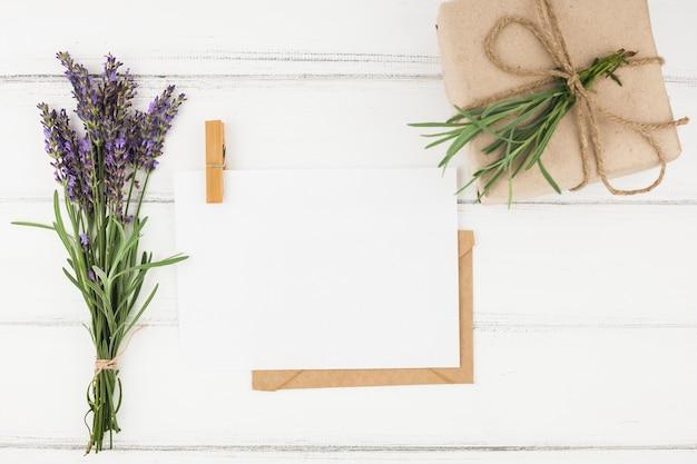 Blumenstrauß aus lavendelblüten; weißbuch und eingewickelter präsentkarton auf holztisch