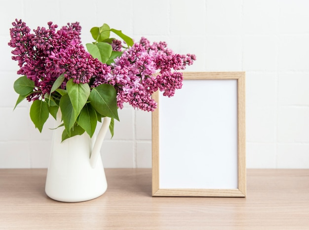 Blumenstrauß aus lila blumen in einer vase und einem leeren rahmen auf einem holztisch.