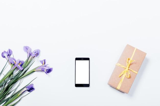 Blumenstrauß aus lila iris, handy und geschenkbox