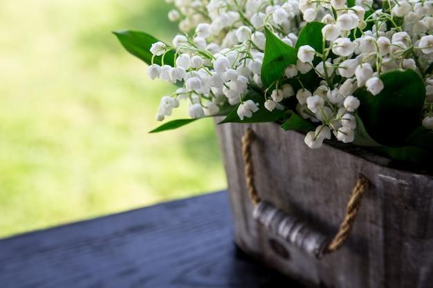 Blumenstrauß aus maiglöckchen in einem korb. blumenhintergrund mit plätzen für ihren text