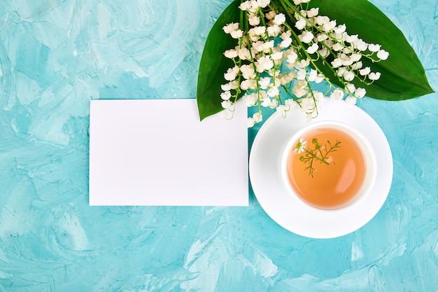 Blumenstrauß aus maiglöckchen und tasse kamillentee.