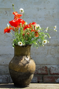 Blumenstrauß aus mohn und gänseblümchen in tonkrug auf rustikalem holztisch gegen alte backsteinmauer