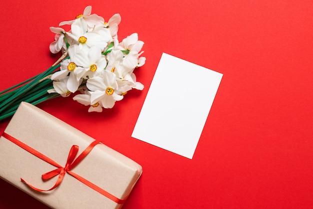 Blumenstrauß aus narzissen, geschenkverpackung und einem blatt papiermodell
