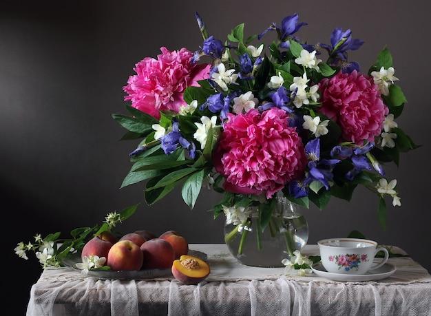 Blumenstrauß aus pfingstrosen, iris und jasmin im glas und pfirsichen auf einem tisch mit spitzentischdecke.