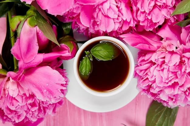 Blumenstrauß aus pfingstrosen und tasse kaffee