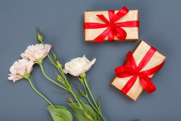 Blumenstrauß aus rosa blumen mit blättern und geschenkboxen mit roten bändern auf grauem hintergrund. ansicht von oben. konzept zum feiertag.
