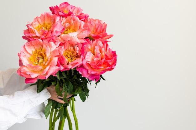 Blumenstrauß aus rosa pfingstrosen in der hand des mädchens auf dem hintergrund einer weißen wandnahaufnahme