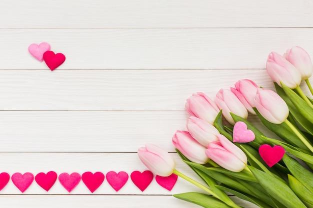 Blumenstrauß aus rosa tulpen mit herzen verziert.