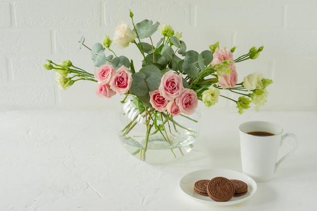 Blumenstrauß aus rosen, eustoma und eukalyptus in einer stilvollen glasvase auf einem tisch. blumenzusammensetzung für die innendekoration.